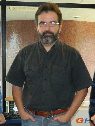 El técnico español al centro de la fotografía de manos en el bolsillo.