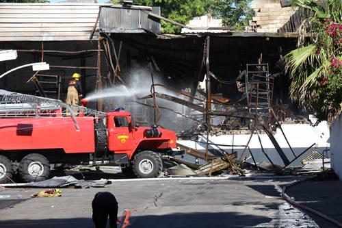Un aspecto del estacionamiento en la tarde de ayer con el trabajo de bomberos aún tratando de apagar cualquier brote de fuego.