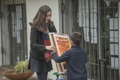 María Inés Curbelo, miembro del grupo de jóvenes de la Comisión de Apoyo al niño con cáncer, recibe el libro de obsequio