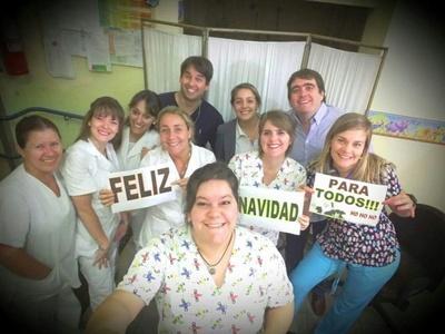 """Lorena con el cartel de """"Feliz"""" junto con los funcionarios colegas del servicio"""