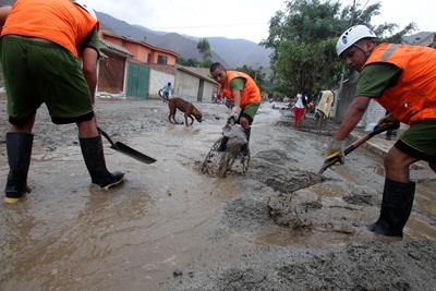 """Brigadistas de la Defensa Civil trabajan en la rehabilitación de una calles luego de un deslizamientos de lodo y piedras conocidos como """"huaicos"""" ayer domingo 22 de enero de 2017, en el kilómetro 27 de la Carretera Central distrito de Chaclacayo, en la ciudad de Lima (Perú). EFE/Germán Falcón."""