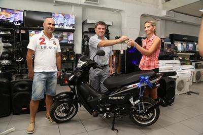El principal de Litnor Hogar Daniel Machado, entregando la llave de la moto  a la esposa del  feliz ganador