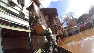 Usando una chalana,  efectivos de las fuerzas armadas proceden a una evacuación.