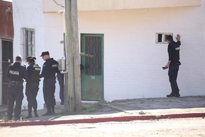 Un policía intenta comunicarse por  medio de una ventana con el atrincherado