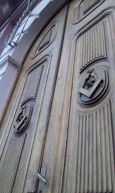 Símbolos masónicos como el compás, la escuadra y la estrella, tallados en la puerta de la Escuela Hiram