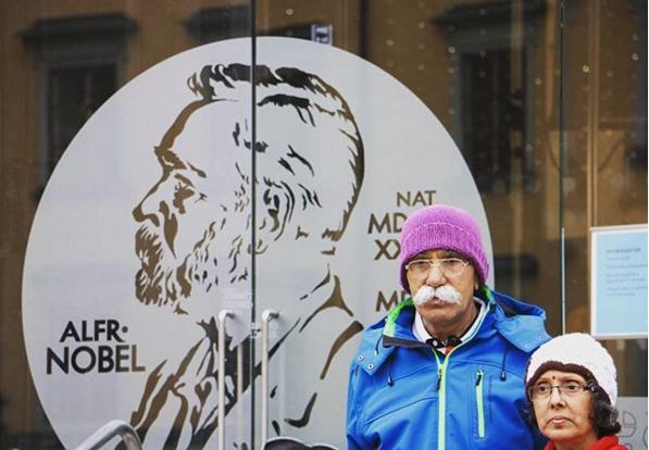 """Un par de turistas se fotografían frente al modesto museo Nobel en el casco antiguo de Estocolmo. En poco coinciden la pequeñez del museo con el prestigio de estos premios. A los moradores de Estocolmo les es imposible ignorar la relación que guardan los premios con la ciudad, ya que año a año Estocolmo se pinta de Nobel vistiendo retratos de los galardonados en sus puntos más transitados. Estocolmo homenajea a destacadas personalidades del globo acatando el mandato de uno de sus más destacados ciudadanos, Alfred Nobel. Alfred Nobel, 1833-1896, empresario e inventor sueco nacido en Estocolmo, acaparó una fortuna considerable gracias a la invención y comercialización de la dinamita, cuyo desarrollo le costó la vida a su hermano Emil en una explosión en 1864. En 1888, Alfred es sorprendido al leer en un periódico su propio obituario, publicado por error tras la muerte de su otro hermano. Este titulaba """"El mercader de la muerte ha muerto"""". Este hecho motivó a Alfred a cambiar la forma en que sería recordado, plasmando en papel y de su propia mano un testamento donde indicaba que su fortuna debía ser invertida en bonos y anualmente sus ganancias se dividirían en 5 premios a ser otorgados a las personas que hayan conferido con su trabajo el mayor beneficio a la humanidad en los campos de Física, Química, Medicina, Literatura y Paz. Su testamento no mandata a entregar premios en matemáticas y economía. Sin embargo el Banco Nacional de Suecia aporta los fondos para éste último. El Nobel de la Paz suele acarrear mayor controversia, ya que busca fomentar la paz o ejercer presión sobre un tema latente, entregándose cuando aún no se ha definido el desenlace. Es el único no otorgado por una academia Sueca, siendo responsable de éste el parlamento Noruego."""