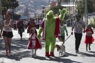"""LA PAZ (BOLIVIA). 17/12/2017.- Un hombre disfrazado del Grinch participa junto a más de 400 ciudadanos bolivianos, caracterizados de Papá Noel, renos, duendes, regalos, Muñecos de Nieve y Reyes Magos, durante la cuarta carrera navideña para incentivar el deporte y el espíritu navideño hoy, domingo 17 de diciembre de 2017, en La Paz (Bolivia). """"Queremos que a través de esta actividad física podamos integrar a la familia, los amigos, y que podamos rescatar el espíritu navideño que debería tener estas fiestas"""", dijo a Efe la directora de deportes de la Alcaldía de La Paz, Jannet Ferrufino. EFE/Martin Alipaz"""