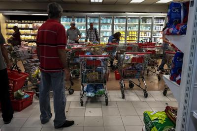 CARACAS (VENEZUELA), 06/01/2018.- Personas buscan alimentos en un supermercado hoy, sábado 6 de enero del 2018, en la ciudad de Caracas (Venezuela). Inspectores del Gobierno venezolano ordenaron este viernes a unas 26 cadenas de supermercados en Venezuela bajar los precios de distintos productos, informó hoy el diario local Últimas Noticias, que no detalla el porcentaje de la rebaja. EFE/Miguel Gutiérrez