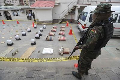 El ministro de gobierno de Bolivia, Carlos Romero (i), observa a policías de la FELCN mientras inspeccionan paquetes de cocaína y marihuana hoy, sábado 20 de enero de 2018, en Cochabamba (Bolivia). La Fuerza Especial de Lucha contra el Narcotráfico (FELCN) de Bolivia decomisó 718 kilos de cocaína y 810 kilos de marihuana en varios operativos realizados esta semana, informó hoy el ministro de Gobierno, Carlos Romero. EFE/Martin Alipaz