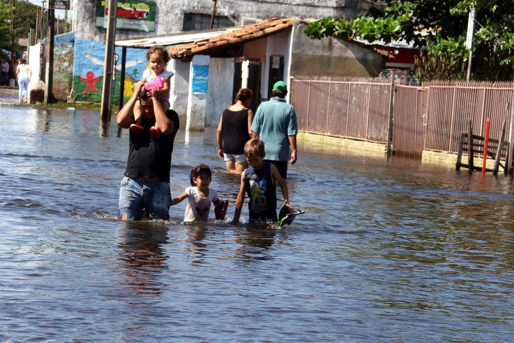 Asunción (Paraguay) - Un grupo de personas camina en una calle inundada el pasado martes 22 de enero de 2018, en un barrio de Asunción (Paraguay). Los vecinos de los Bañados de Asunción, barrios ribereños en las orillas del río Paraguay, se afanan después de una semana de inundaciones, en mudarse a zonas más altas de la ciudad mientras algunas zonas ya se encuentran totalmente anegadas por el agua y las casas abandonadas tras la crecida. EFE/Andrés Cristaldo